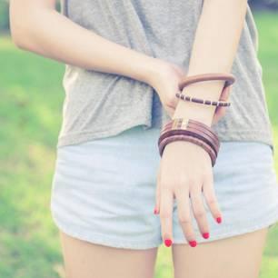 Erste Periode: Eine junge Frau fasst sich ans Handgelenk
