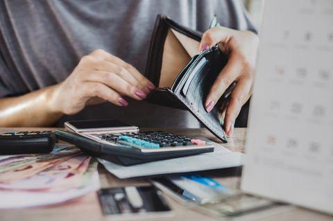 Schuldenfalle: Frau schaut in leeren Geldbeutel