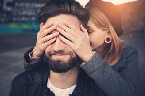 AXA-Partnerschaftsstudie: Eine Frau hält ihrem Schatz von hinten die Augen zu