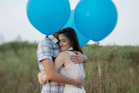 Wie beendet man einen unnötigen Streit? Ein Pärchen umarmt sich umgeben von blauen Luftballons