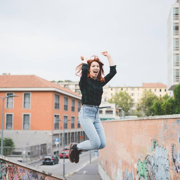 Selbstwertgefühl stärken: Eine junge Frau springt in die Luft