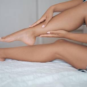 Geschwollene Beine: Frau tastet Beine ab