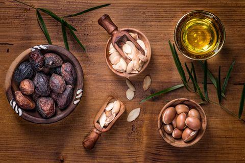 Arganöl für die Haut: Argannüsse, Argankerne und Arganöl in einer Schale stehen auf einem Holztisch
