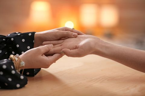 Handlesen: Eine Frau hält eine andere Frauenhand und analysiert ihre Handfläche