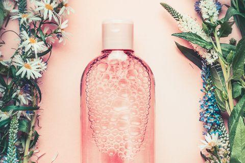 Gesichtswasser selber machen: Flasche mit durchsichtiger Flüssigkeit auf rosa Untergrund, umgeben von Blumen