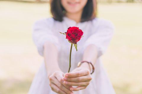 Jemanden verliebt machen – geht das? Frau hält Rose in der Hand