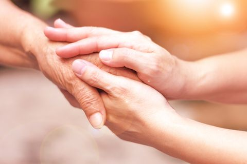 Hospiz Pflegerin und Seniorin halten Hände