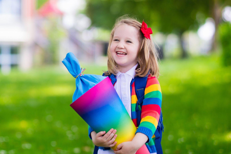 Schultüte nähen: Mädchen lacht und hält eine Schultüte in der Hand