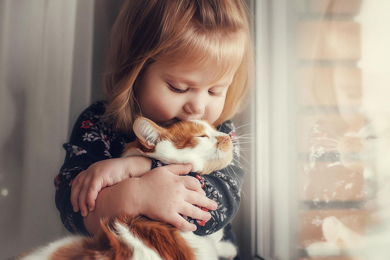 Kinderweisheiten über die Liebe: Mädchen kuschelt mit Katze