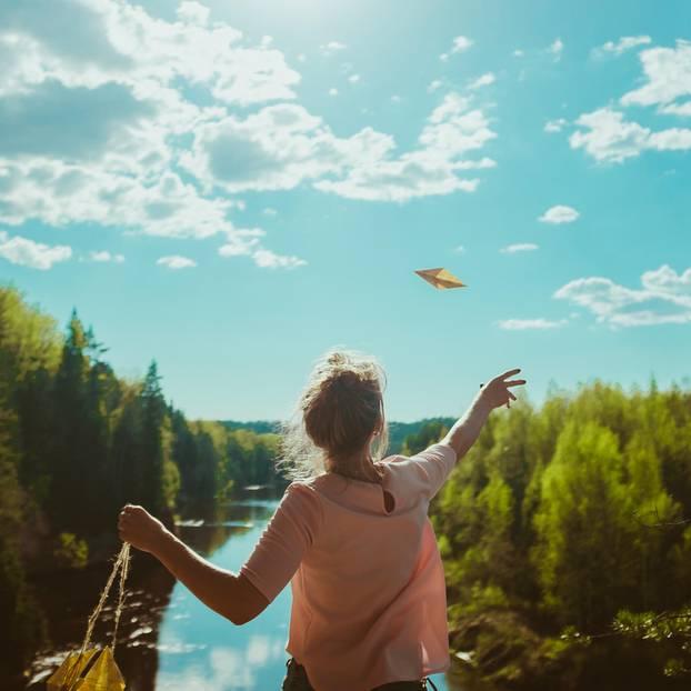 Was ist Glück? Eine junge Frau am Fluss wirft einen Papierflieger in die Luft