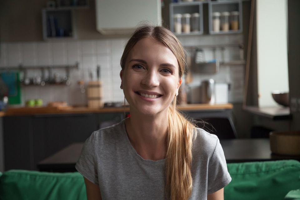 WG-Casting: Junge Frau sitzt lächelnd auf einem Sofa in der Küche