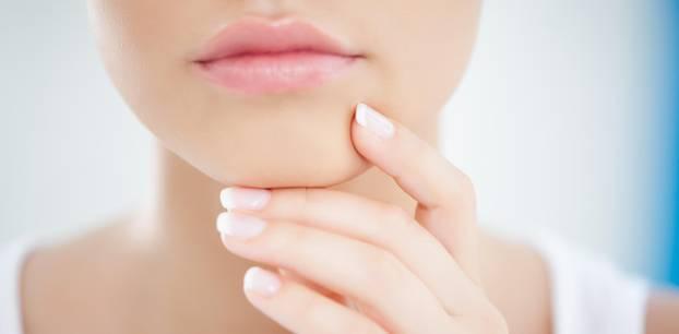 Komedogen: Frau mit reiner Haut hält sich Hand an den Kiefer