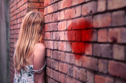 Unerwiderte Liebe: Eine junge Frau steht mit dem Gesicht zur Wand