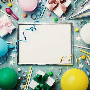 Geburtstag vergessen: Leerer Bilderrahmen umgeben von Partydeko und kleinen Geschenkverpackungen