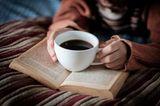 Frau hält eine Tasse Kaffee in der Hand