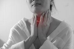 Geschwollene Lymphknoten: Frau tastet Hals ab