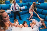 Hochzeitsfoto: Braut auf Hüpfburg und Gäste