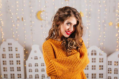 Mondkalender Haare: Frau mit wallenden Haaren steht vor Wand mit Lichterketten und Deko-Monden und -Sternen