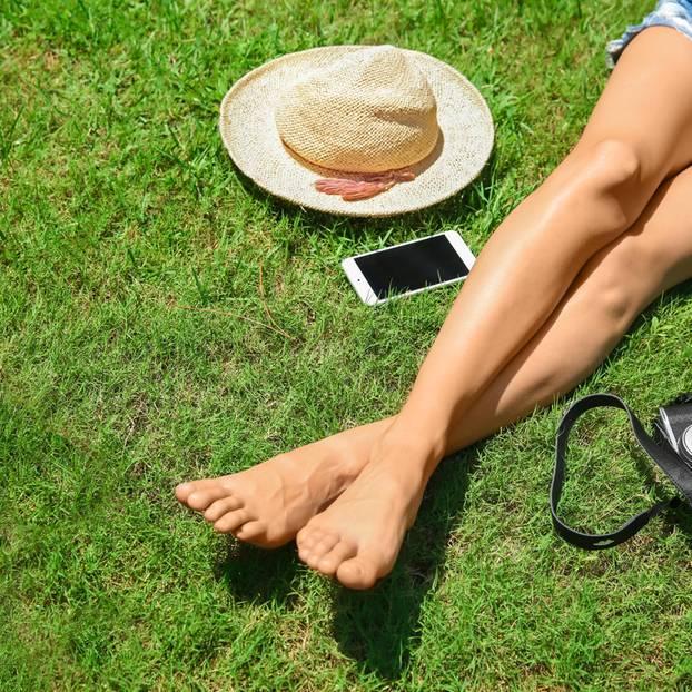Sonnenallergie vorbeugen: Frau sonnt sich auf Wiese