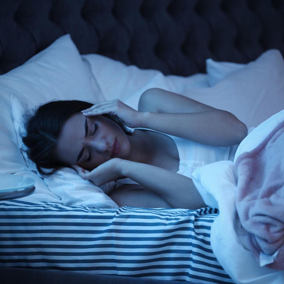 Migräne-Symptome: Frau liegt im Dunklen