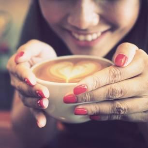 Kaffee für dein Sternzeichen: Frau hält Kaffeetasse in der Hand
