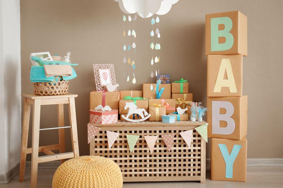 Geschenke zur Geburt - Gschenke auf einer Holzbox gestapelt, daneben große Letter und das Wort Baby