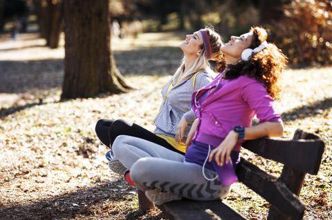 Die größten Stärken der Jungfrau: Zwei Freundinnen in Sportklamotten auf einer Bank