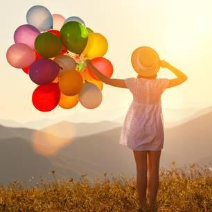 Horoskop: Eine Frau mit Luftballons auf einem Berg
