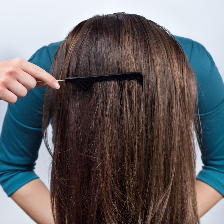Einfache Frisuren: Frau beugt sich mit offenen Haaren nach vorne und wird gekämmt