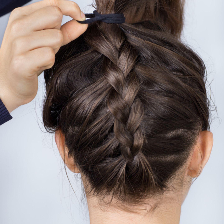 Einfache Frisuren: Geflochtener Zopf wird mit einem Haarband zusammengebunden
