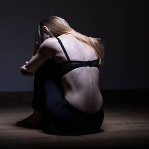 Magersucht: Sehr dünne Frau sitzt auf dem Boden