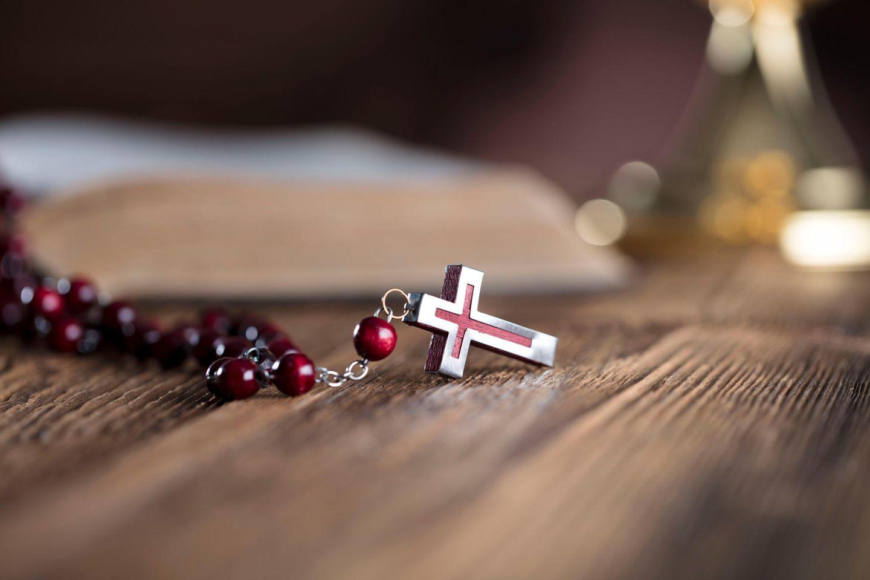 Glückwünsche zur Konfirmation: Kreuzanhänger liegt auf Tisch