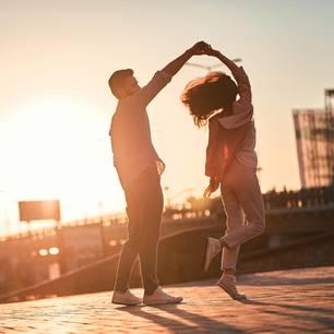 Attraktivität: Zwei Menschen tanzen im Sonnenuntergang
