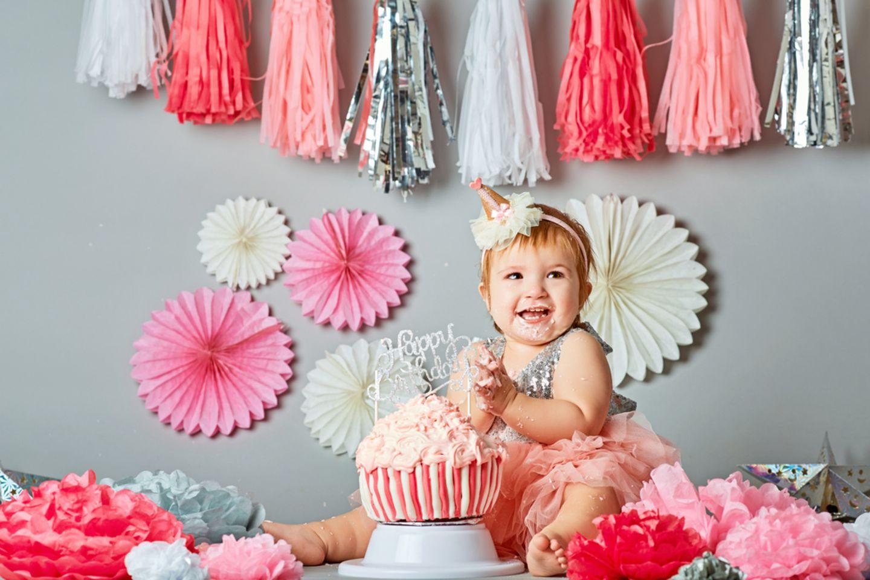 Geschenke zum 1. Geburtstag: Kleinkind sitzt vor Geburtstagskuchen und lacht