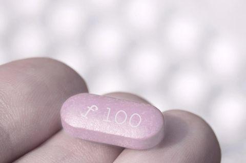 Viagra für Frauen: Frau hält pinke PIlle in der Hand