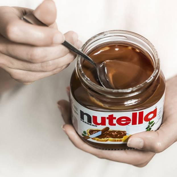Frauenhand mit Löffel im Nutella-Glas