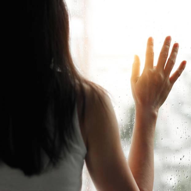 Depression behandeln: Traurige Frau am Fenster