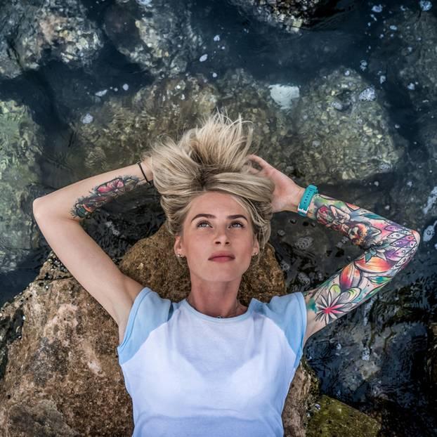 Was Tattoos über Menschen aussagen: Tätowierte Frau liegt am Wasser