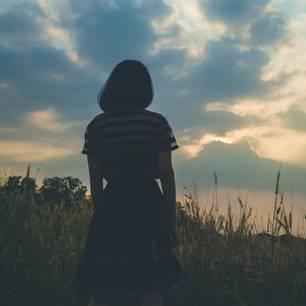 Frau steht und schaut auf den Himmel