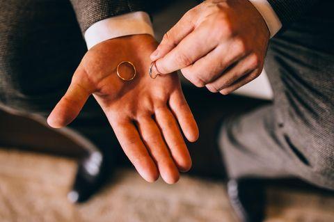 Whisper: Ein Mann mit zwei Eheringen in der Hand