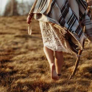 Indianische Weisheiten: Eine Indianerin mit Feder in der Hand von hinten