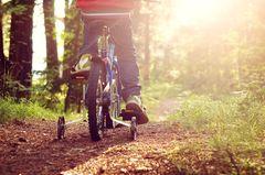 Fahrrad fahren lernen: Junge fährt mit Stützrädern