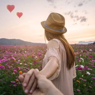 Horoskop: Eine Frau führt ihren Freund über eine Blumenwiese
