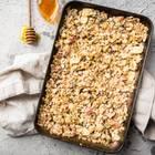Baked Oatmeal: Auflaufform mit Haferflockenauflauf von oben, daneben ein Glas mit Honig