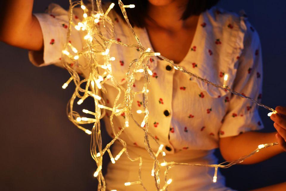 Lichterkette basteln: Frau mit Lichterkette