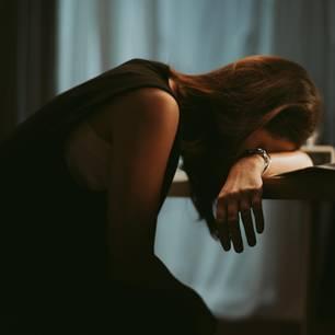 Burnout-Symptome: Erschöpfte Frau im Büro