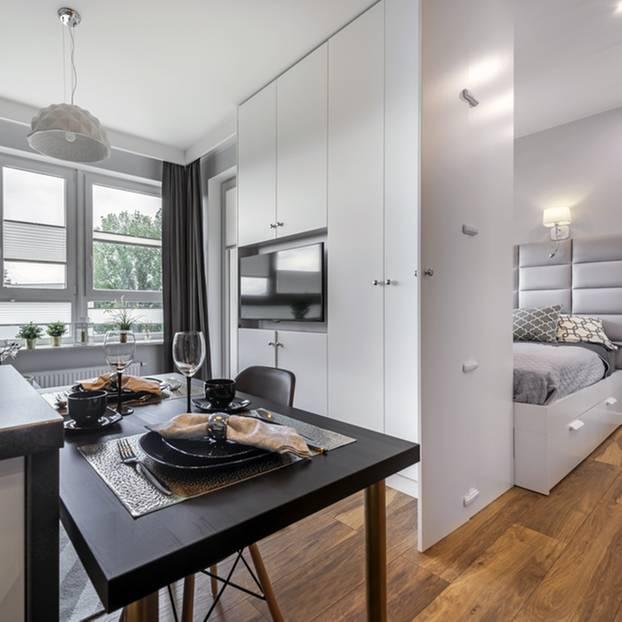 Einzimmerwohnung einrichten: Zimmer mit links Couch und Esstisch, in der Mitte ein Schrank und rechts ein Bett