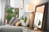 Einzimmerwohnung einrichten: Beistelltisch auf dem eine kleine Lampe und ein Spiegel steht