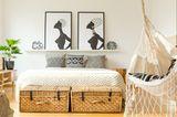 Einzimmerwohnung einrichten: Zwei große Boxen stehen vor einem Bett, über diesem hängen zwei Bilder