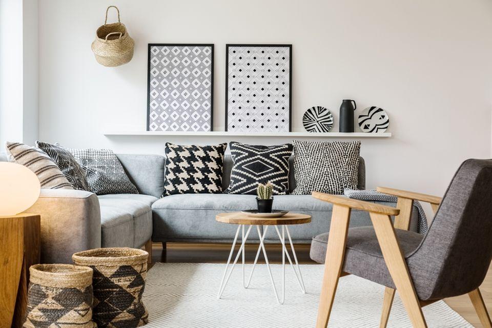 Einzimmerwohnung einrichten: Graue Couch in der Mitte ein kleiner Tisch und ein Sessel